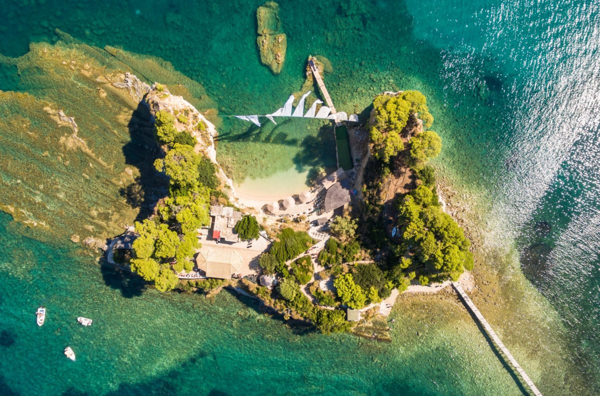 Small Greek islet surrounded by clear green water